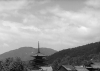 Shot of a Japanese pagoda (in Kyoto), set among ordinary rooftops and trees, with tree-lined mountains and sky in the background.