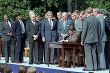 Rangel en ongeveer veertien andere mannen staan rond een tafel, waar president Ronald Reagan een wet tekent signs