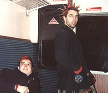 Two young men dressed in black trenchcoats are shown in a subway car. The man on the left has bright red dyed hair. The man on the right also has bright red dyed hair, but his hair is in long pointed spikes.