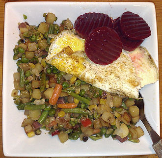 Pyttipanna - A plate of pyttipanna with vegetables, sliced beet, and a fried egg