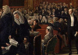 "Pains and Penalties Bill 1820 - A detail from ""The Trial of Queen Caroline 1820"" by Sir George Hayter—left to right: Stephen Lushington (in wig with back to painter); Henry Brougham (in wig handing sheet of paper downwards); William Vizard, the Queen's solicitor (on floor beneath Brougham); Lord Chancellor Lord Eldon (seated in centre background facing front); Queen Caroline; Lord Grey (with extended arm)."