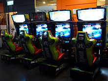 Four arcade cabinets with seats and steering wheels in a row, colored green