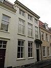 Huis met witgeschilderde lijstgevel en eenvoudige ingangsomlijsting