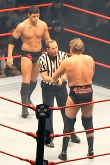 Two men face off in a wrestling ring with a referee between them. The one facing the camera has short black hair, and is wearing short black wrestling tights with the letters 'CR' upon them in pink with black boots and a black elbow pad on his right arm. The man facing away from the camera has longer, light brown hair and the word 'villain' is written upon the back of his short black wrestling tights.