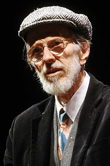 An elderly man with a white beard, round glasses, and beret-like hat.