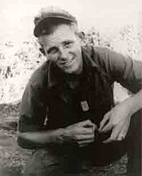 A smiling young man in military uniform, crouching with his forearms resting on his legs. His soft cap is pushed high up on his forehead and his dog tags hang out of his short-sleeved button shirt.