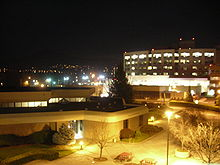 The photo was taken during the night. A large building in the foreground is brightly lit, with a much larger building behind it, and city lights in the background
