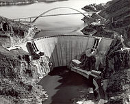 The downstream face of renovated Roosevelt Dam, with a concrete face. A bridge spanning Lake Roosevelt is seen in the background.
