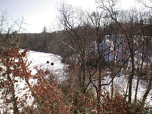 Southern New England Railway - Looking south along the Blackstone River, with the SNE embankment at right and several unfinished supports in the river