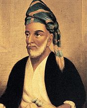 A portrait of a bearded man wearing a turban or headscarf