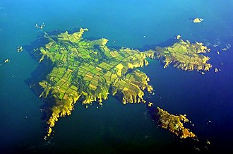 Sark - September 2005 aerial view of Sark. North is to the lower left, Little Sark toward the upper right and Brecqhou at bottom right.
