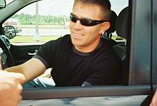 A man in his thirties with a head full of hair. He is wearing sunglasses and a black T-shirt and is shaking hands with another person.