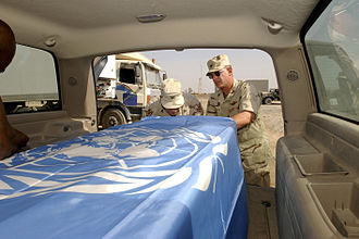 Canal Hotel bombing - U.S. officers secure a United Nations flag over the transfer case of Sérgio Vieira de Mello, prior to a memorial service at the Baghdad International Airport.