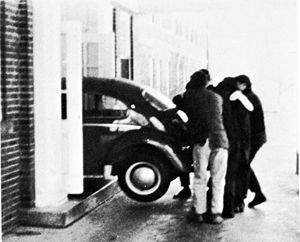 Practical joke - Shimer College students pushing a VW Beetle into a campus building