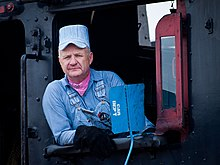 Steam locomotive driver wearing a popular shade of light blue and white  striped seersucker overalls and engineer cap 6609379e00b2