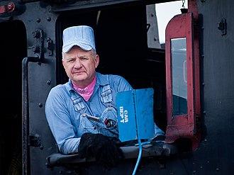 Seersucker - Steam locomotive driver wearing a popular shade of light blue and white striped seersucker overalls and engineer cap