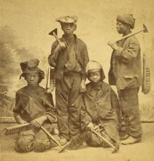 Chimney sweep -  A studio portrait of four New York climbing boys, with brushes and scrapers