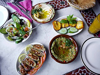 Makdous - A Syrian meal, with makdous at the lower left of center. Continuing clockwise are salad, hummus, haloumi and baba ganouj, with pita bread partially visible at upper right corner of photo.