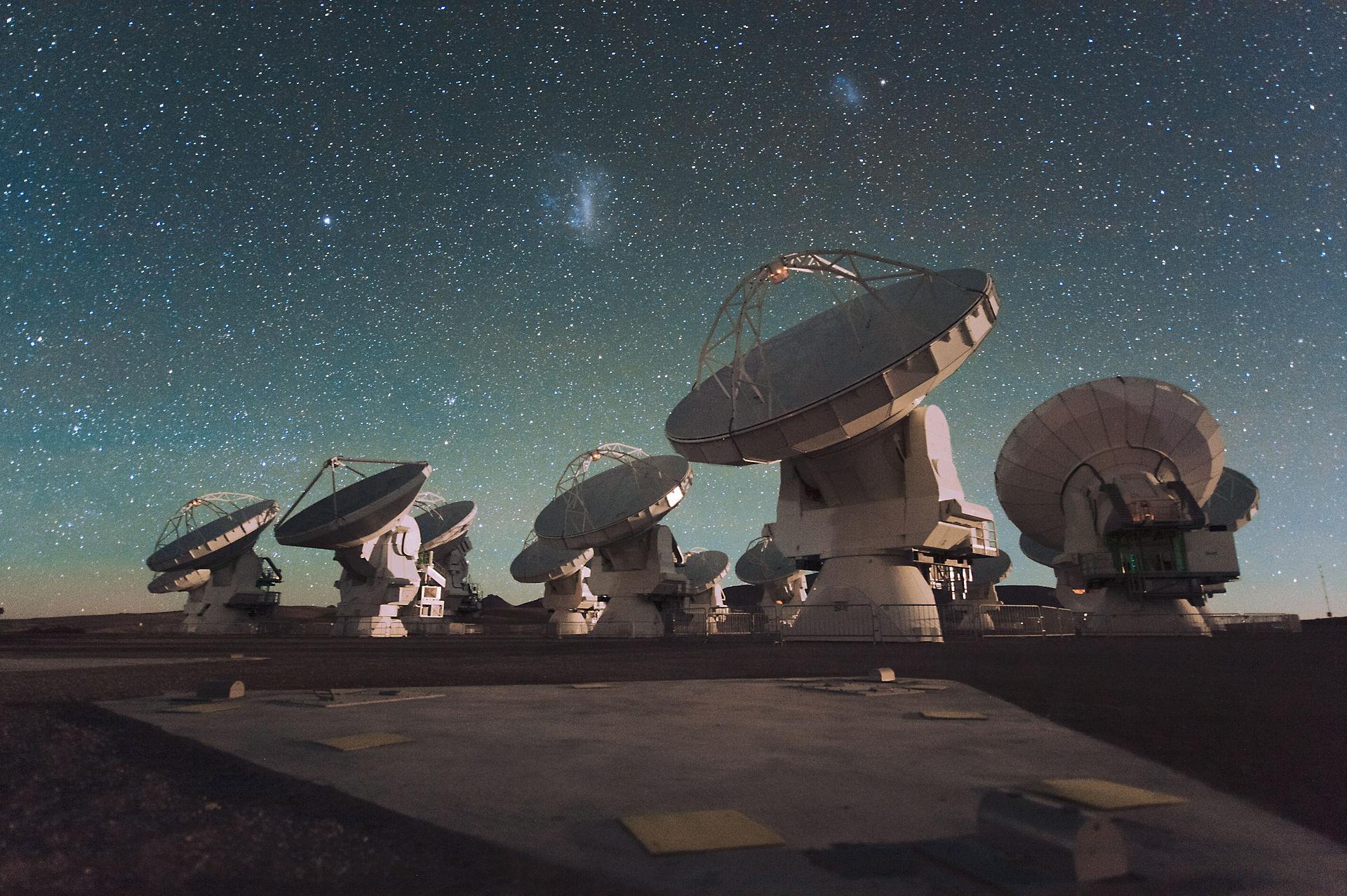 ALMA-Antennen bei Nacht unter den Magellanschen Wolken