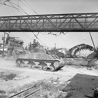 16th/5th The Queen's Royal Lancers - An M4 Sherman tank of the 16th/5th The Queen's Royal Lancers passes through a railway yard at Arezzo, Italy, 15–16 July 1944.