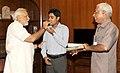 The Prime Minister, Shri Narendra Modi congratulates Shri Rajesh Kumar, son of PMO Daftary who has cleared the civil services examination, in New Delhi on June 25, 2014.jpg