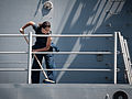 U.S. Navy Seaman Lucirelia Sosa sweeps water off the deck during a fresh water wash down aboard the guided missile destroyer USS Stockdale (DDG 106) May 23, 2013, while operating in the U.S. 5th Fleet area 130523-N-HN991-032.jpg