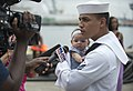 U.S. Navy Ship's Serviceman Seaman Richard Berrios, right, assigned to the amphibious dock landing ship USS Pearl Harbor (LSD 52), holds his daughter during an interview in San Diego after returning from 130826-N-ZU025-153.jpg
