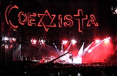 "A view of the stage being filmed, with ""COEXISTA"" spelled out on the video screen, using an Islmaic crescent as a ""C"", a Star of David as an ""X"", and a Christian cross at a ""T"". A camera in the middle shows the concert being filmed."