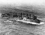 Three-quarter overhead view of destroyer with four funnels and damaged bow, at sea