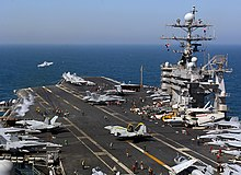 F/A-18 Hornet launches from the flight deck of USS  Harry S. Truman. Other aircraft are stored on deck.