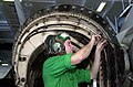 US Navy 030310-N-2143T-001 Aviation Structural Mechanic 3rd Class Jesse Weber works on the tail section of an F-A-18 Hornet in the ship's hanger bay.jpg