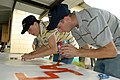 US Navy 070823-N-9486C-075 Mineman 1st Class Ammie Faucett and Electrician's Mate 3rd Class Levi Martin of High Speed Vessel (HSV) 2 Swift paint a sign during a community relations project at the Hogar de Ninos San Ramon orphan.jpg
