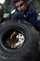 US Navy 090123-N-3946H-026 Aviation Support Equipment Technician Airman Joseph Zaliagiris changes the tire of an aircraft spotting dolly.jpg