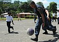 US Navy 100825-N-2074H-411 Naval Aircrewman 3rd Class Tony Arango, from El Paso, Texas, embarked aboard the amphibious assault ship USS Iwo Jima (LHD 7), plays basketball with a group of students from Hone Creek primary school.jpg