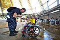 US Navy 110718-N-RM525-156 Lt. Erinn Gelakoska, from St. Louis, fist bumps a Salvadoran child who just received a new wheelchair during a Continuin.jpg