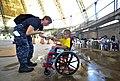 US Navy 110718-N-RM525-156 Lt. Erinn Gelakoska, from St. Louis, fist bumps a Salvadoran child who just received a new wheelchair during a Continuin.jpg