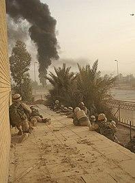 Soldados estadounidenses observan cómo el cuartel general paramilitar iraquí quema Samawah, Irak, abril de 2003.jpg