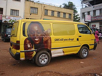 Economy of Africa - A mobile phone advertisement on the side of a van, Kampala, Uganda.