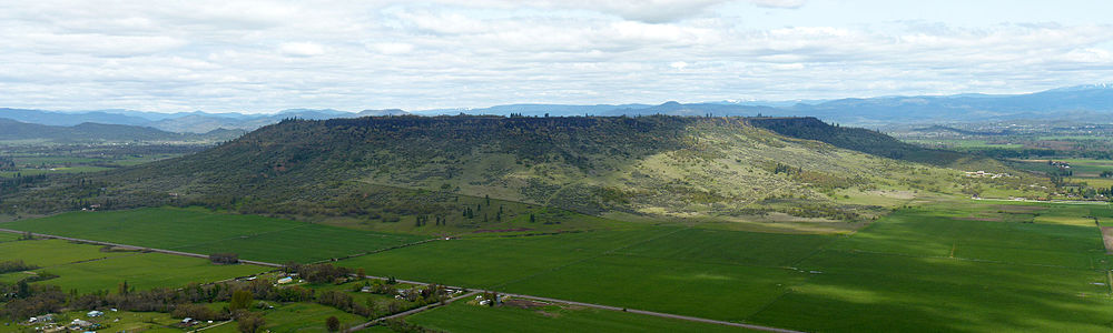 A large flat topped plateau with trees scattered on its flanks and farmland below it
