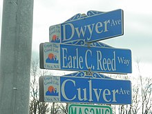 Three street signs on a pole