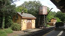 A water tower adjacent to railroad track