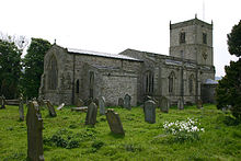 A long stone church in a graveyard, see from the northeast, with a north vestry, and a tower at the far end