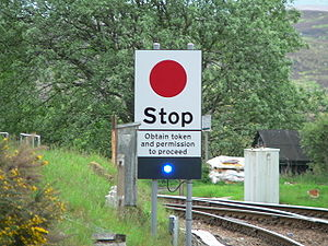 Radio Electronic Token Block - A Stop Board marking the start of a radio token section at Rannoch railway station on the West Highland Line. The blue light is a TPWS status indicator.
