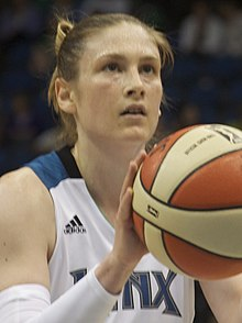 Young woman wearing white Lynx basketball uniform and her hair up preparing to shoot