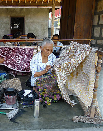 Batik - Batik craftswomen in Java drawing intricate patterns using canting and wax that are kept hot and liquid in a heated small pan.