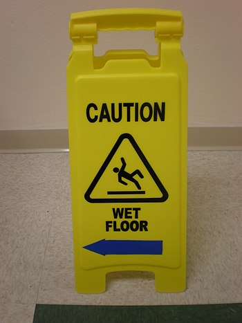 A portable plastic sign warning of a wet floor...