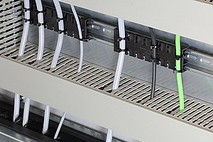 Cable management - Strain relief plate inside an electrical enclosure, mounted on a 35 mm DIN rail shape H.