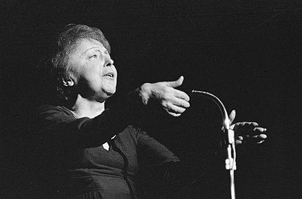 Edith Piaf singing in front of a microphone (1962). Edith Piaf 914-6436.jpg