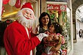 'Santa Claus' loving a child at Cannaught Place during the eve of the Christmas, in New Delhi on December 24, 2006.jpg