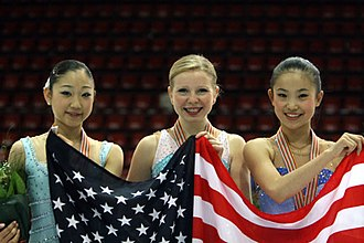 2008 World Junior Figure Skating Championships - The ladies' medalists hold up the American flag. From left: Mirai Nagasu (3rd), Rachael Flatt (1st), Caroline Zhang (2nd).